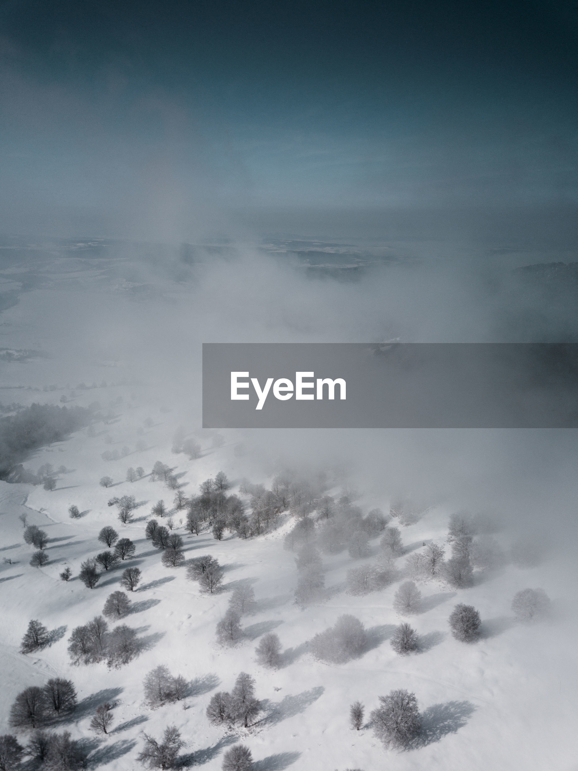 AERIAL VIEW OF FOG COVERED LANDSCAPE