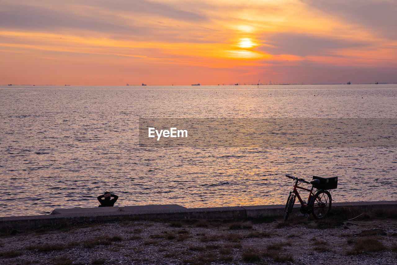 sky, sunset, water, beauty in nature, sea, orange color, scenics - nature, cloud - sky, nature, horizon, bicycle, mode of transportation, silhouette, horizon over water, transportation, idyllic, beach, land, tranquility, outdoors, no people