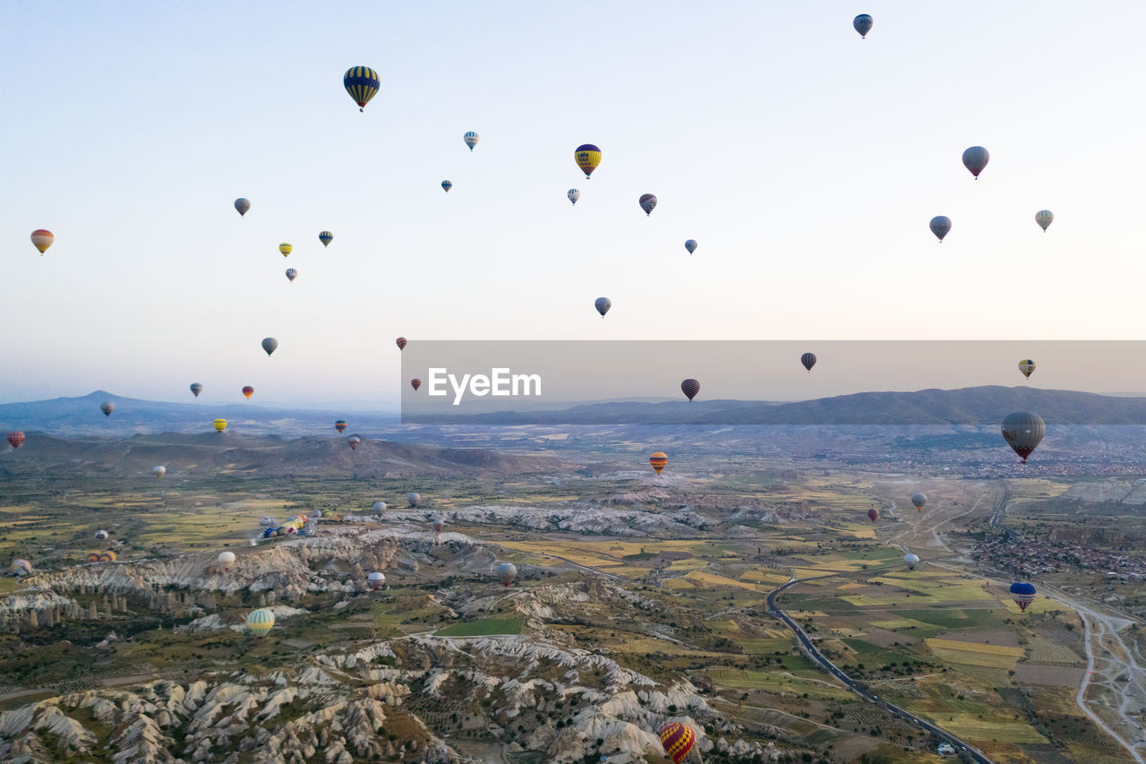 balloon, air vehicle, hot air balloon, mid-air, flying, sky, ballooning festival, nature, landscape, transportation, environment, no people, rock formation, rock - object, rock, scenics - nature, beauty in nature, solid, day, mountain, outdoors