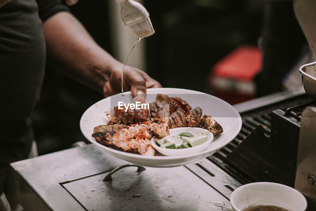 food and drink, food, human hand, hand, one person, real people, freshness, holding, ready-to-eat, table, midsection, indoors, meat, human body part, lifestyles, business, plate, serving size, restaurant, crockery