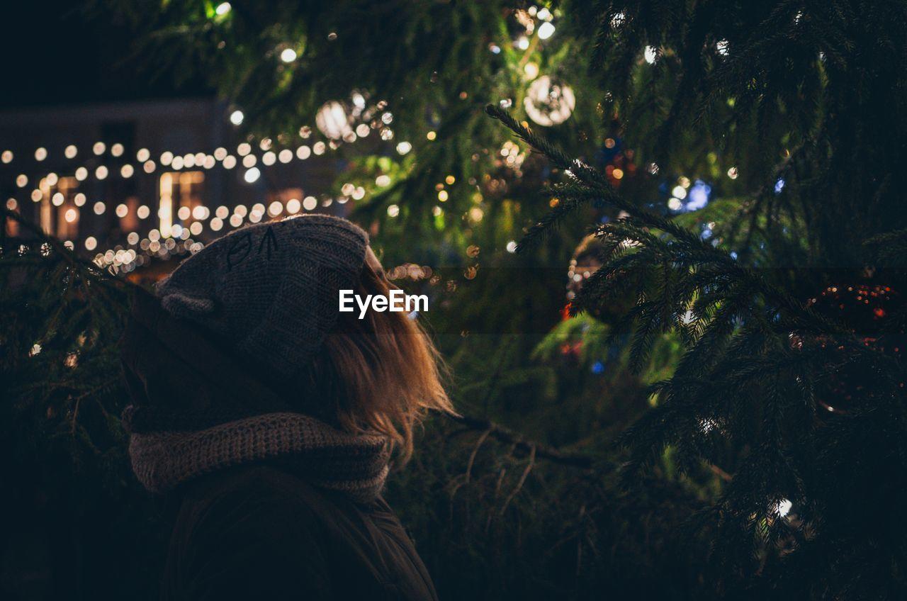 Woman Looking At Christmas Tree At Night