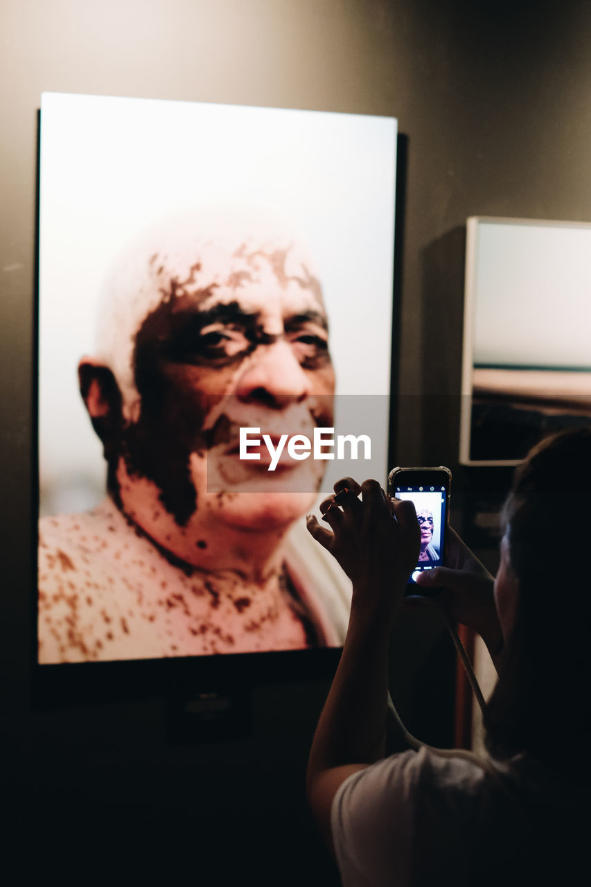 technology, photography themes, real people, holding, indoors, wireless technology, communication, portrait, smart phone, photographing, activity, connection, adult, mobile phone, women, one person, portable information device, headshot, lifestyles