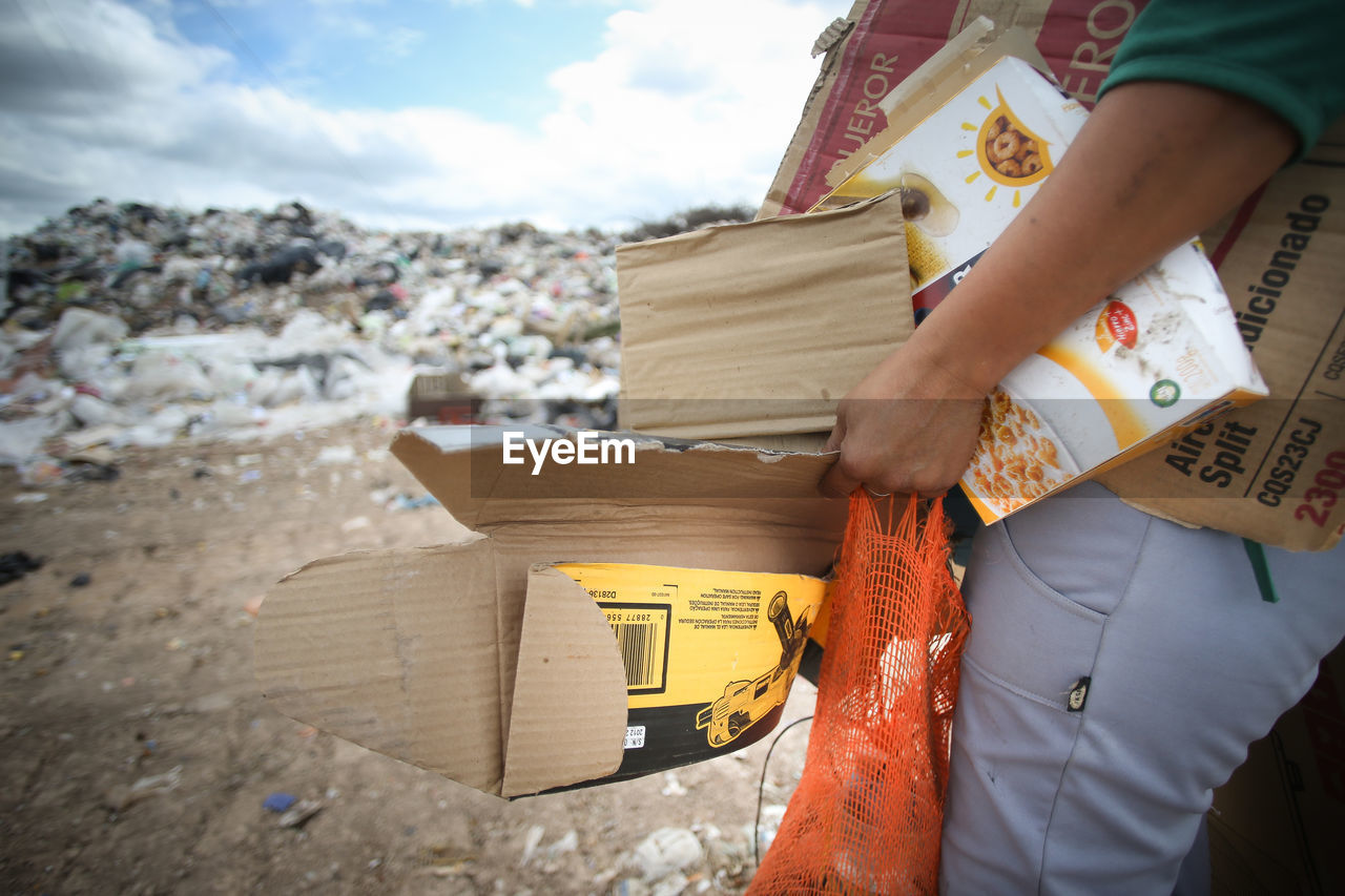 Midsection of man holding garbage against sky