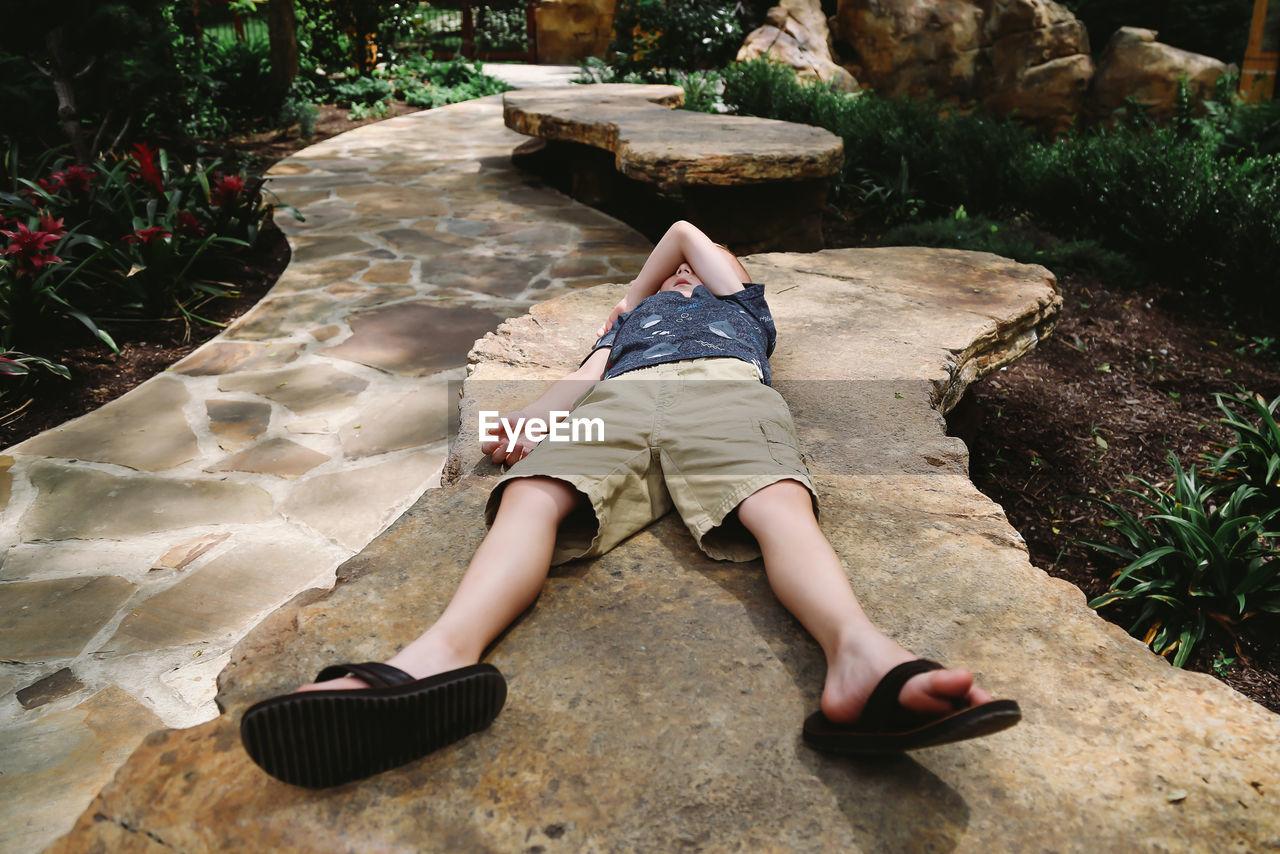 Boy sleeping on seat in park
