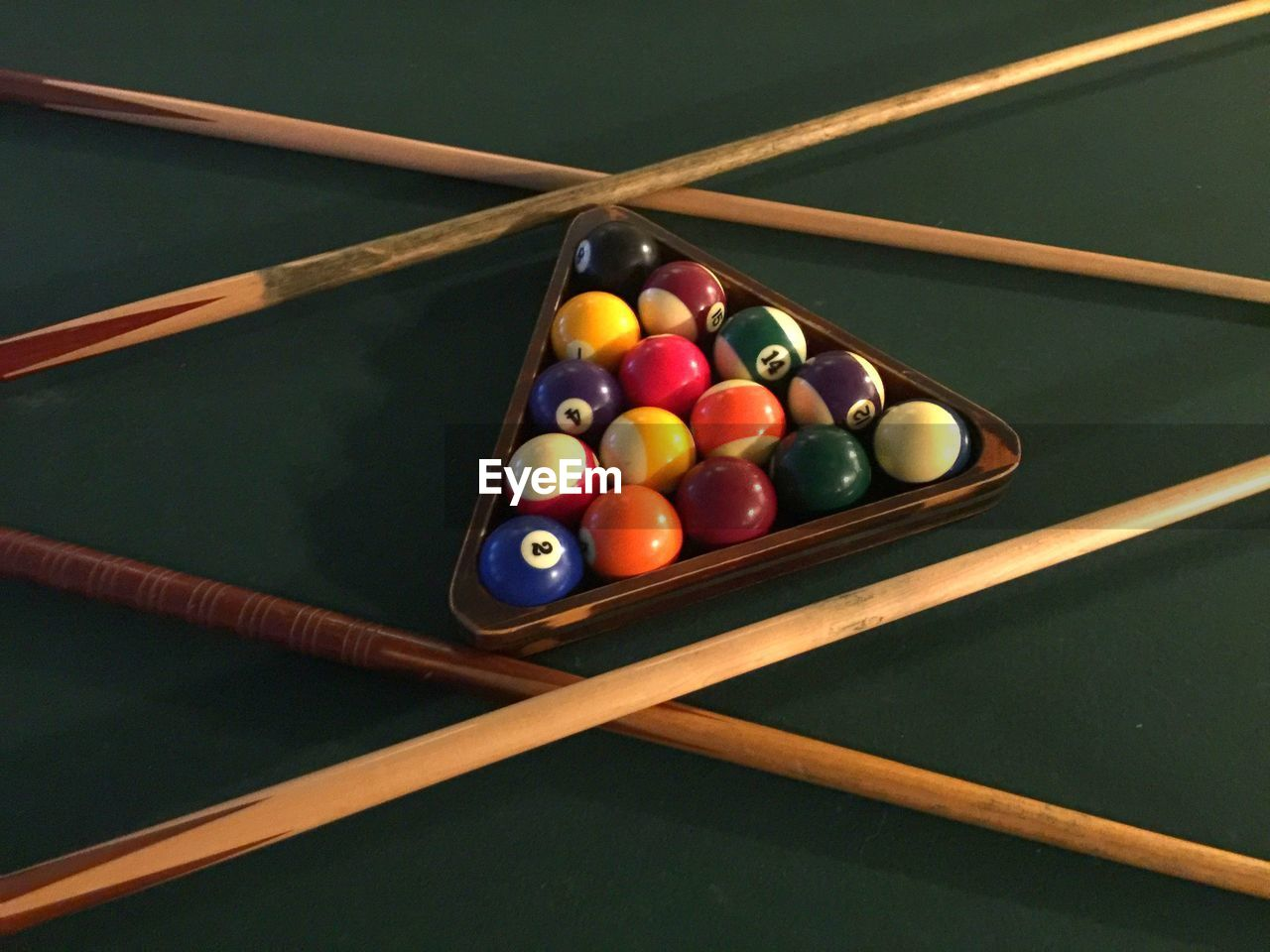 ball, indoors, table, multi colored, pool - cue sport, pool ball, still life, no people, pool table, sport, high angle view, large group of objects, wood - material, leisure games, sphere, triangle shape, arrangement, shape, pool cue, leisure activity