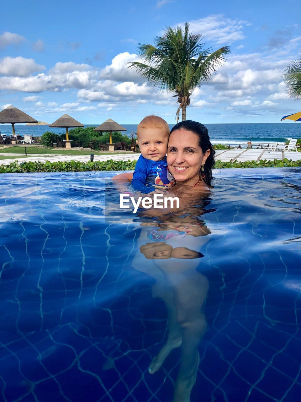 Portrait of smiling mother and son in swimming pool against sky