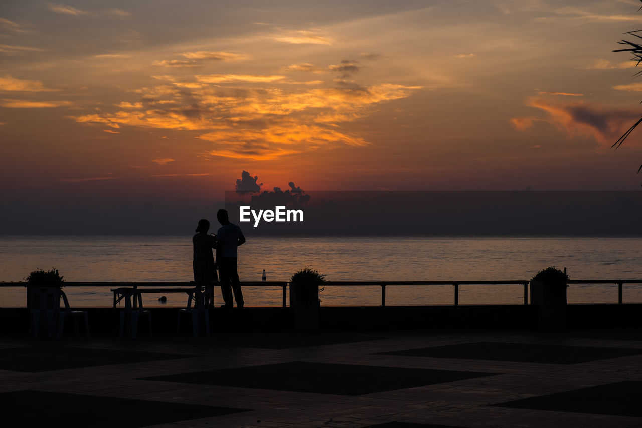 sunset, sky, water, sea, beauty in nature, scenics - nature, real people, orange color, cloud - sky, horizon over water, men, group of people, standing, horizon, lifestyles, leisure activity, railing, silhouette, nature, outdoors, looking at view