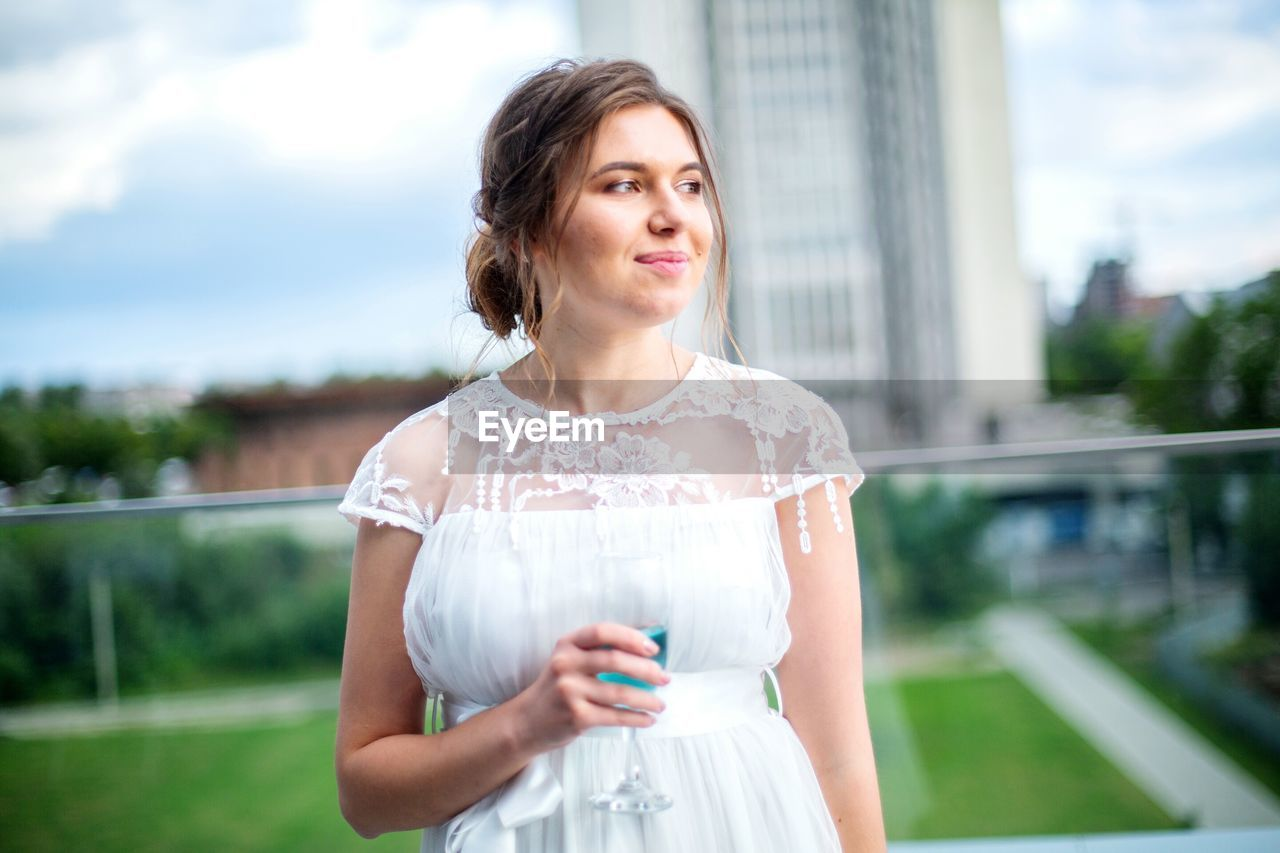 Beautiful Woman Holding Drink Looking Away While Standing Outdoors
