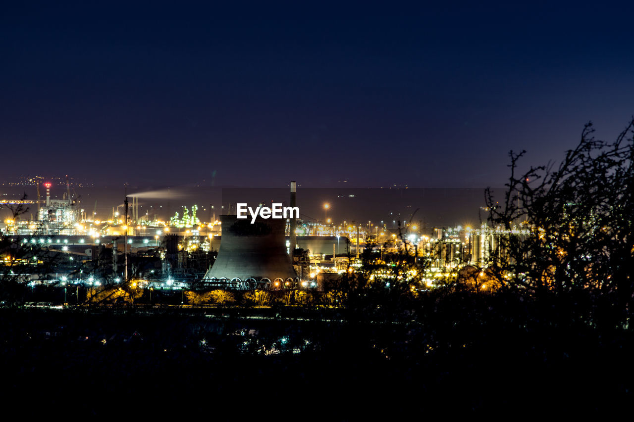 night, building exterior, illuminated, sky, factory, architecture, industry, built structure, no people, fuel and power generation, nature, smoke stack, outdoors, high angle view, power station, environmental issues, copy space, city, pollution, plant, industrial district