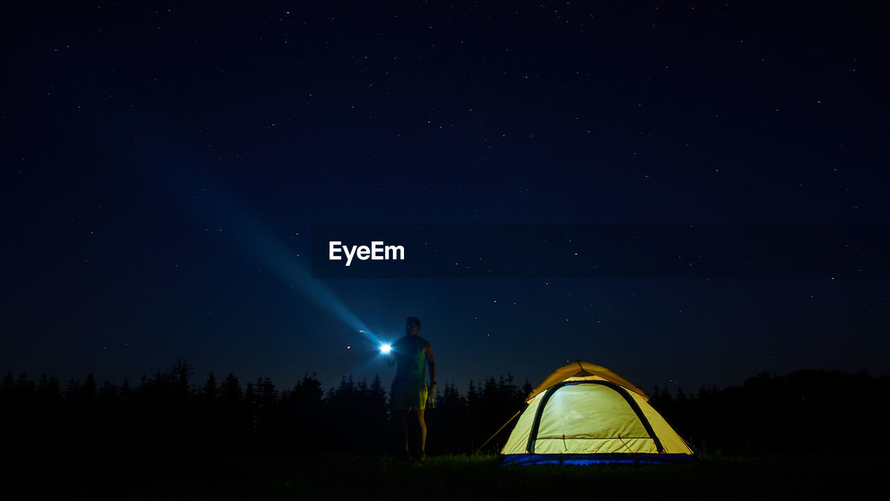 Full Length Of Man Flashing Light In Sky While Standing By Tent At Night