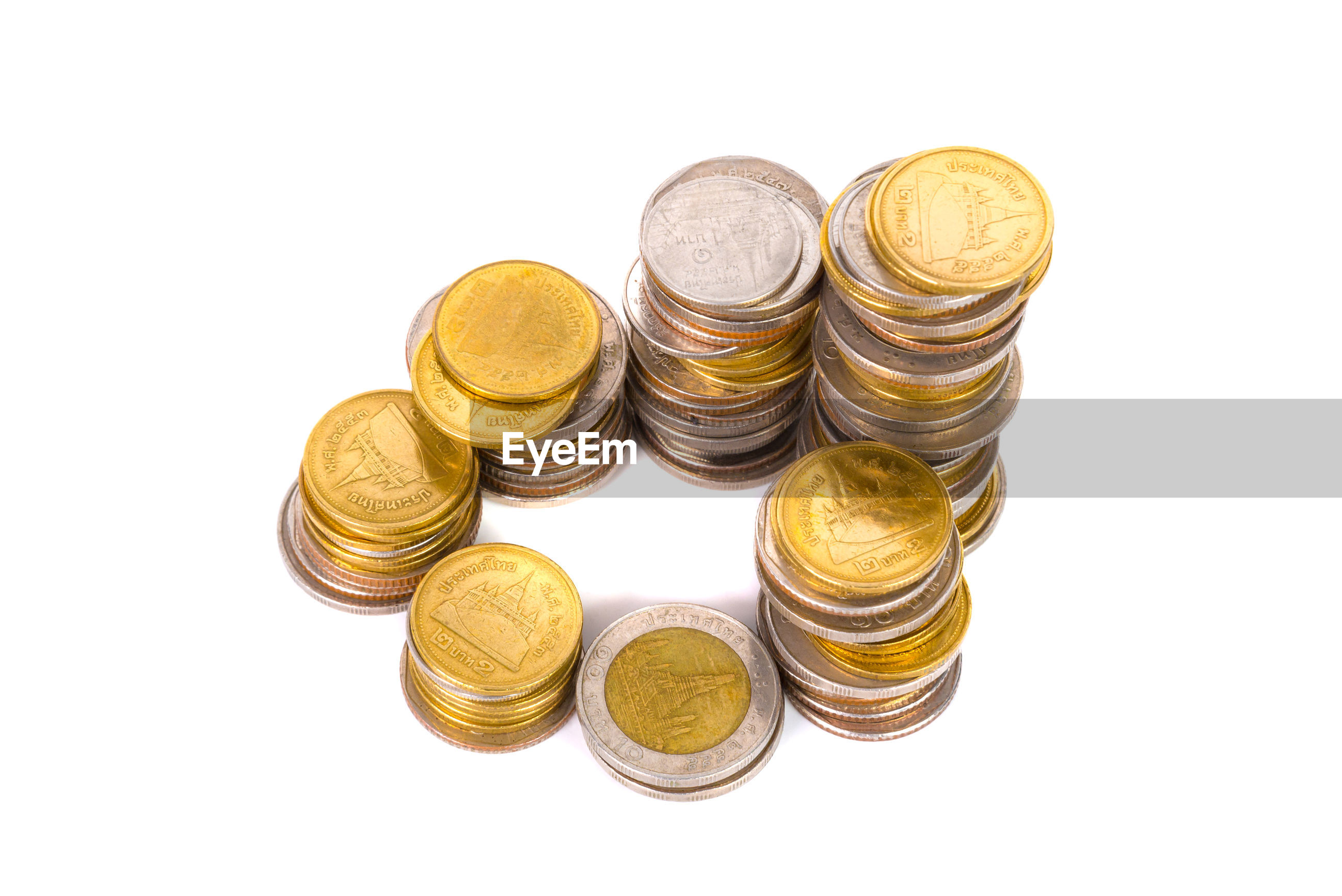 High angle view of stacked coins on white background