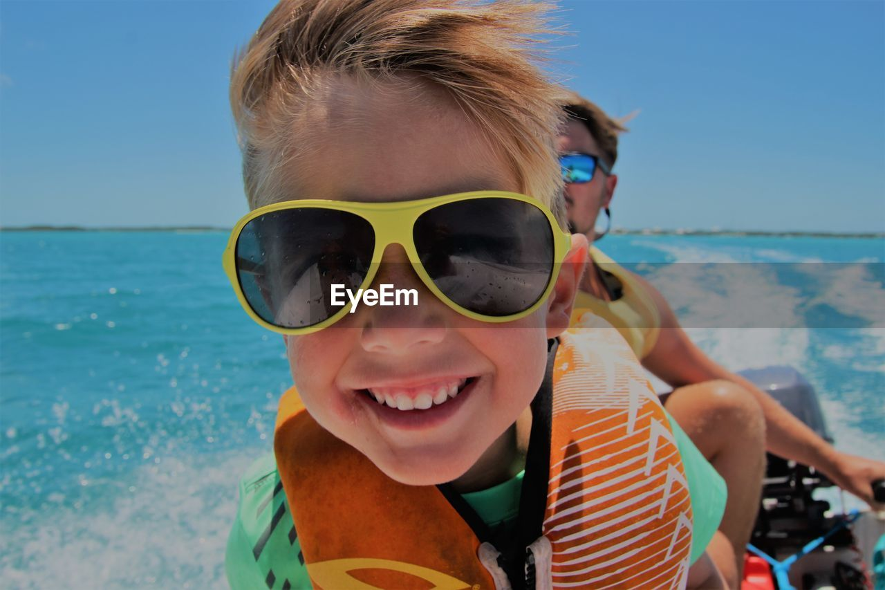 Close-up portrait of smiling boy wearing sunglasses while traveling in boat