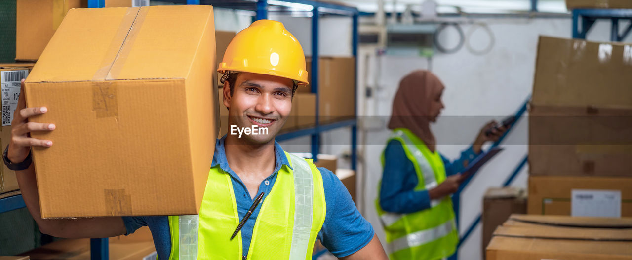 Portrait of smiling worker carrying box in factory