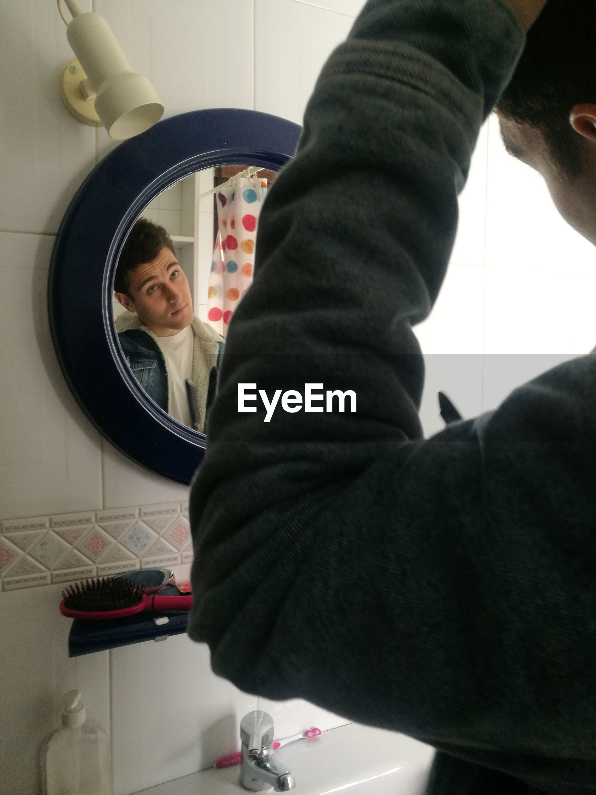 Man combing hair in bathroom at home