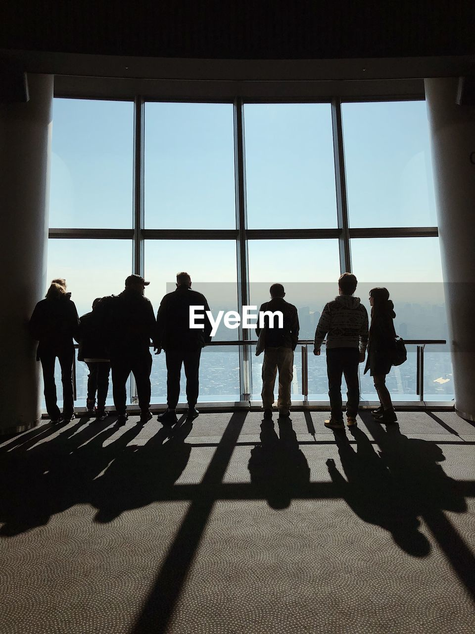 Silhouette people against window in building