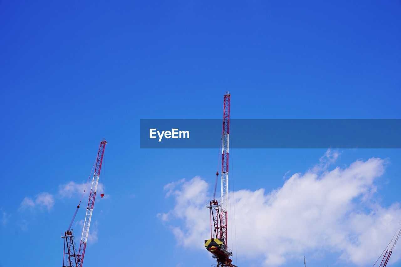 sky, industry, low angle view, blue, architecture, built structure, cloud - sky, construction industry, machinery, crane - construction machinery, day, nature, tall - high, no people, technology, broadcasting, tower, communication, development, building exterior, outdoors, industrial equipment, construction equipment, global communications
