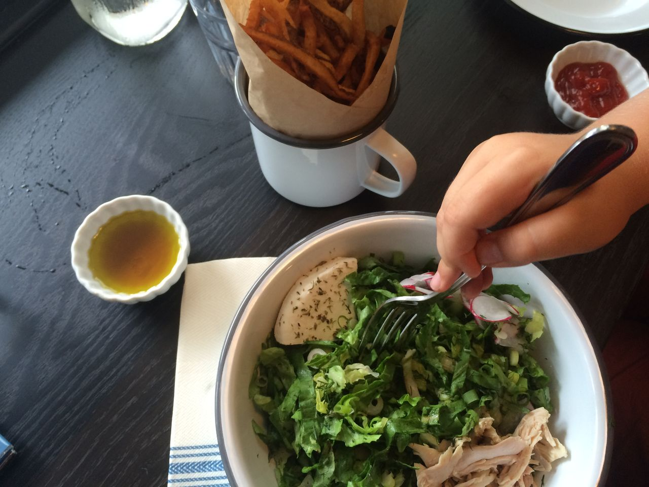 Cropped image of hand holding fork in food on table