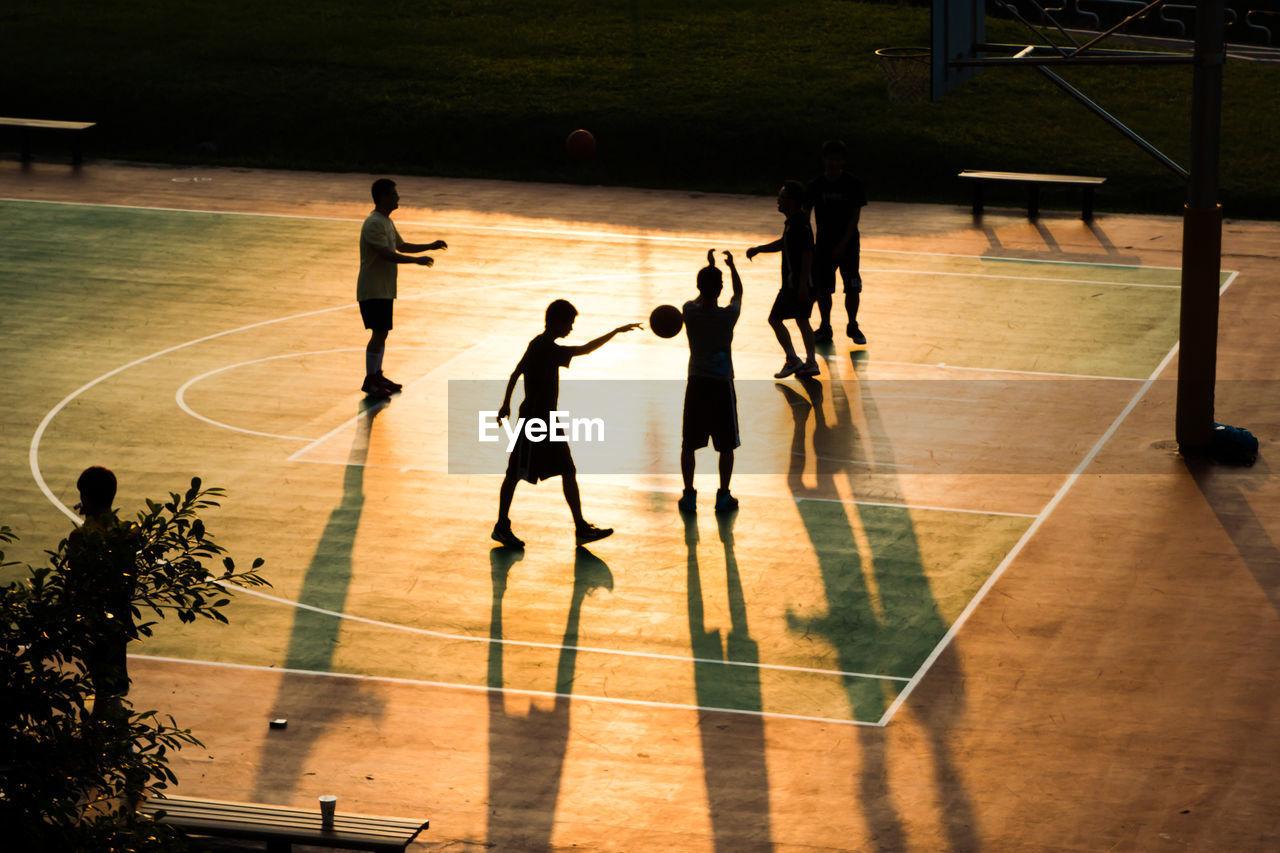 Silhouette boys playing basketball