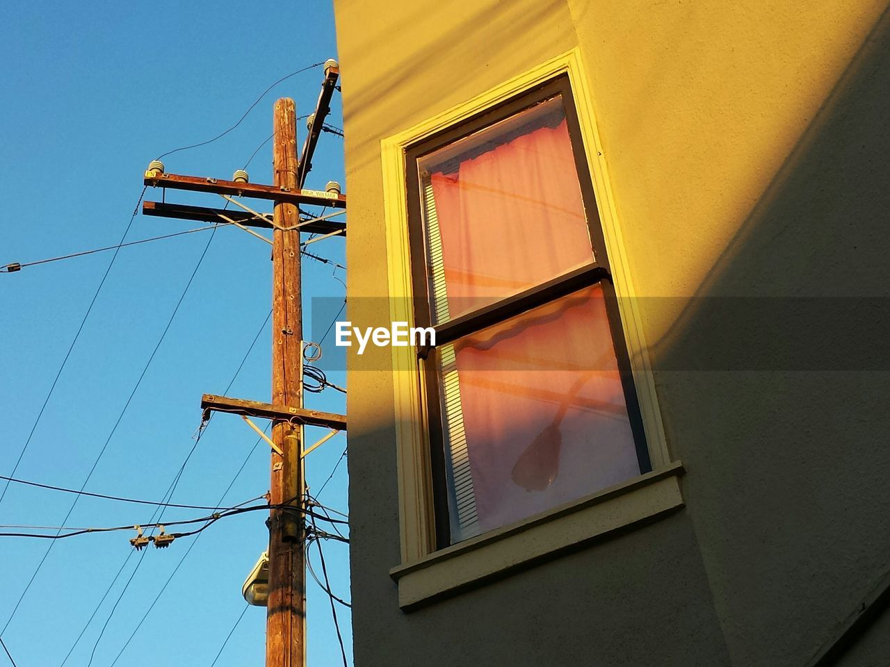 Low angle view of telephone pole by building against sky