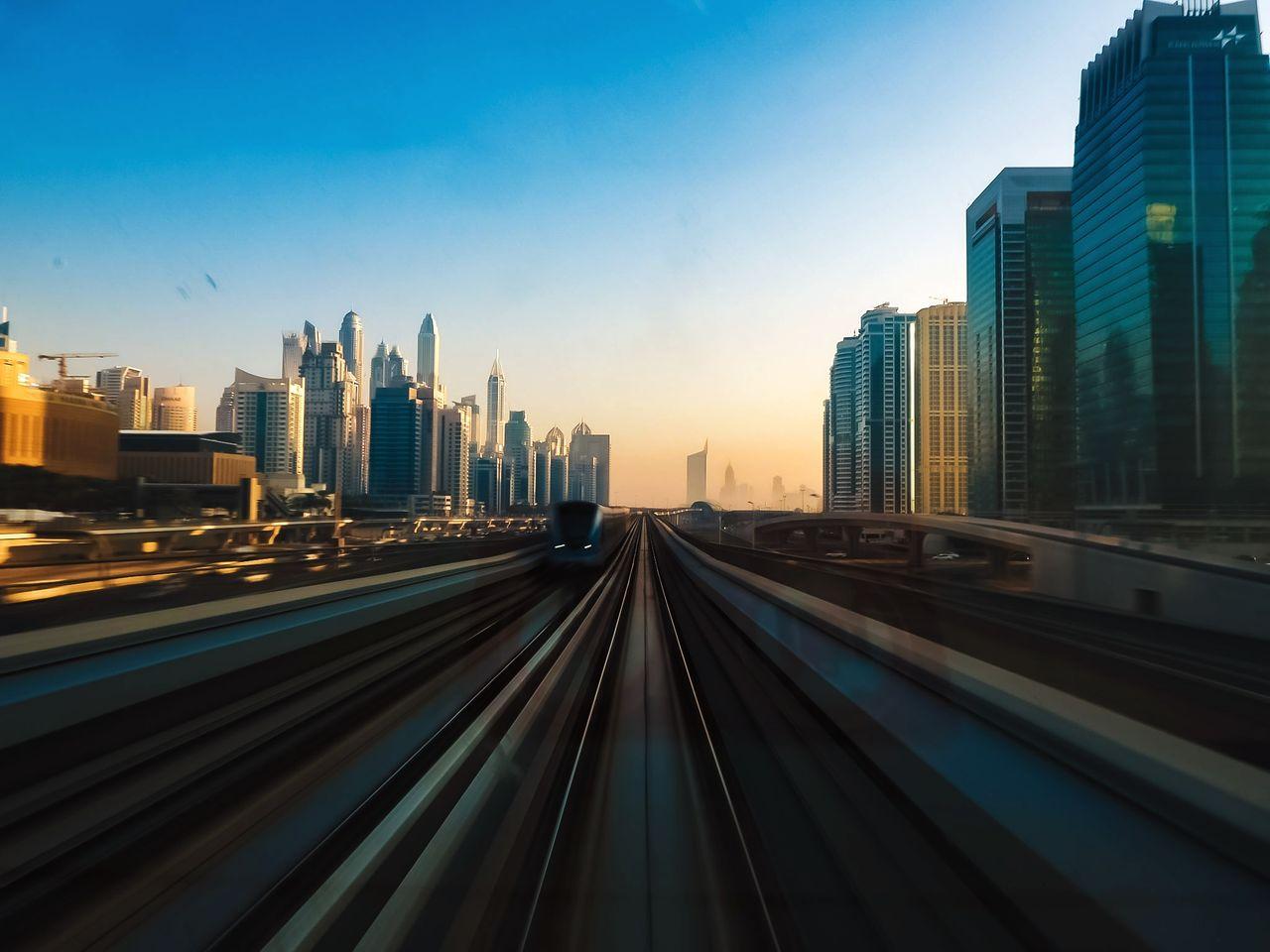 LIGHT TRAILS ON CITY AGAINST BLUE SKY