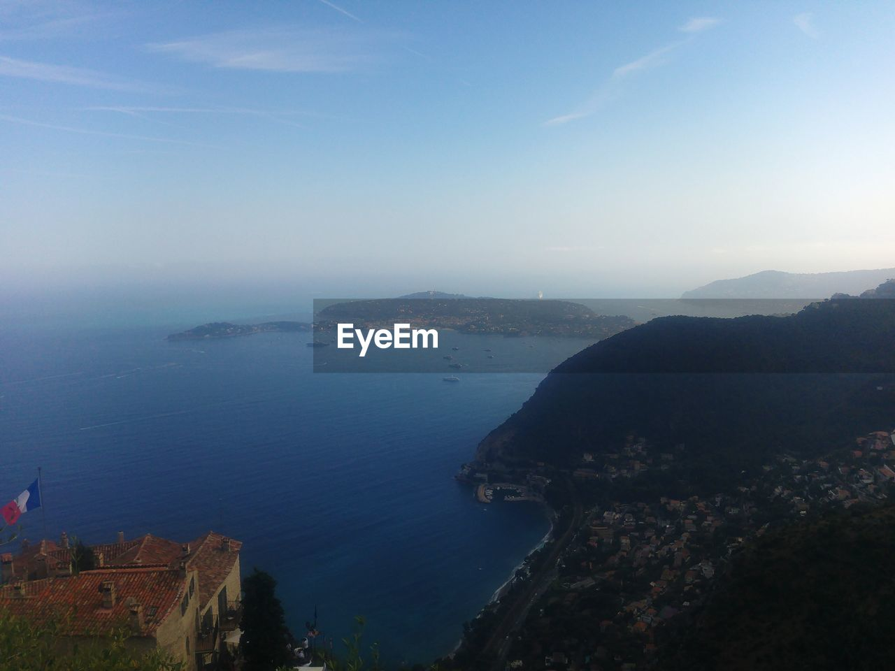 HIGH ANGLE VIEW OF SEA BY MOUNTAINS AGAINST SKY