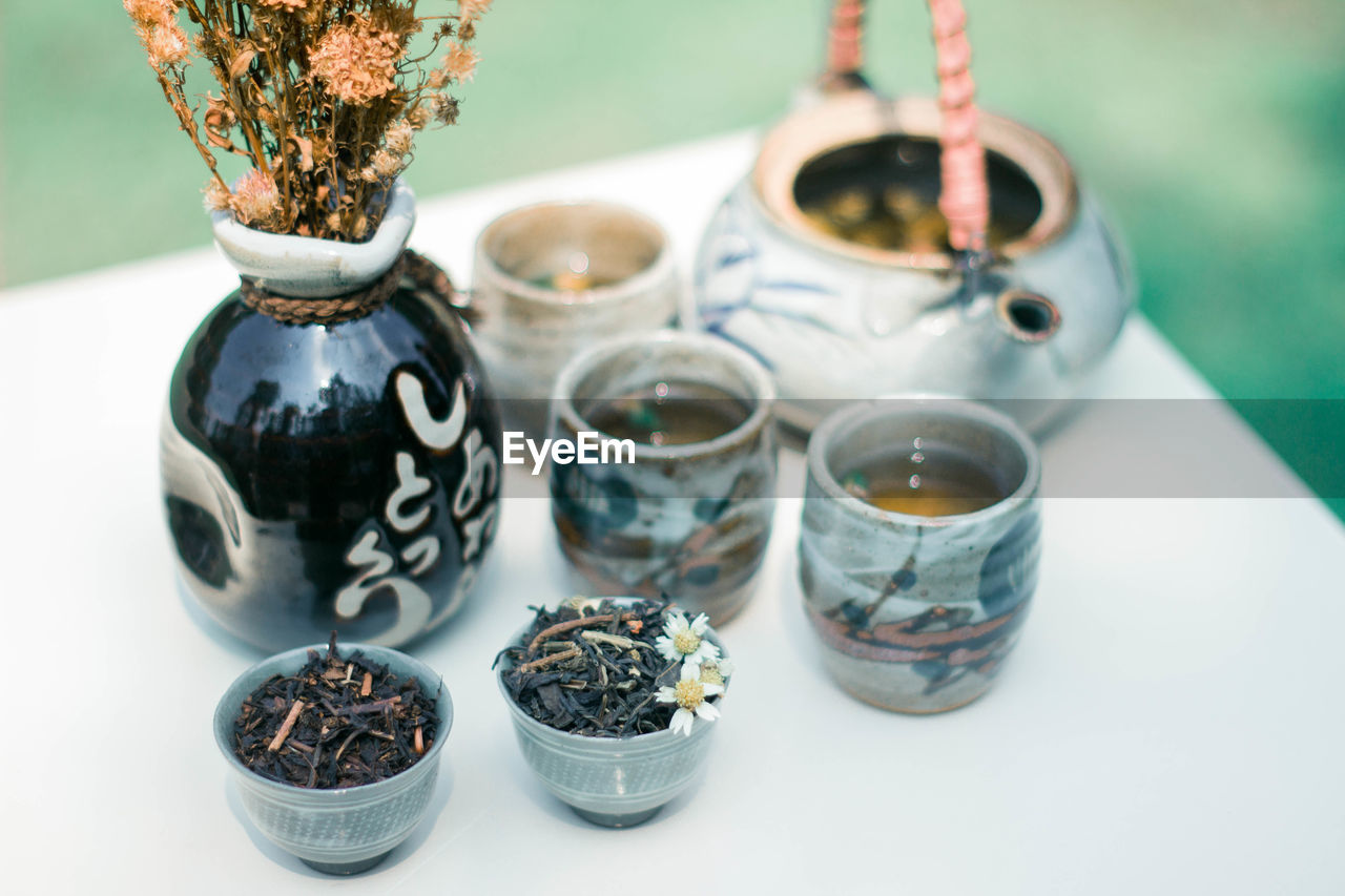 table, indoors, still life, no people, food and drink, cup, drink, close-up, container, refreshment, focus on foreground, tea, hot drink, nature, food, plant, mug, tea - hot drink, transparent, teapot, tea leaves, crockery