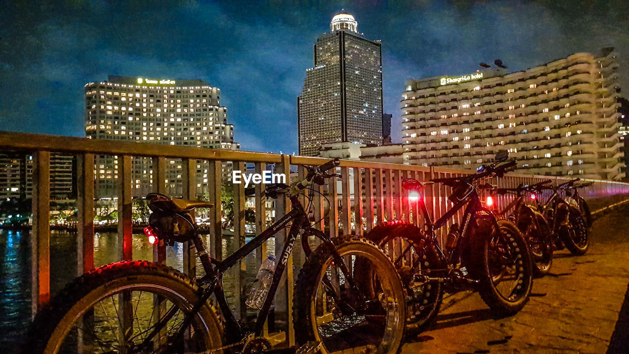 bicycle, architecture, transportation, building exterior, built structure, mode of transport, land vehicle, city, sky, outdoors, illuminated, stationary, night, no people, bicycle rack