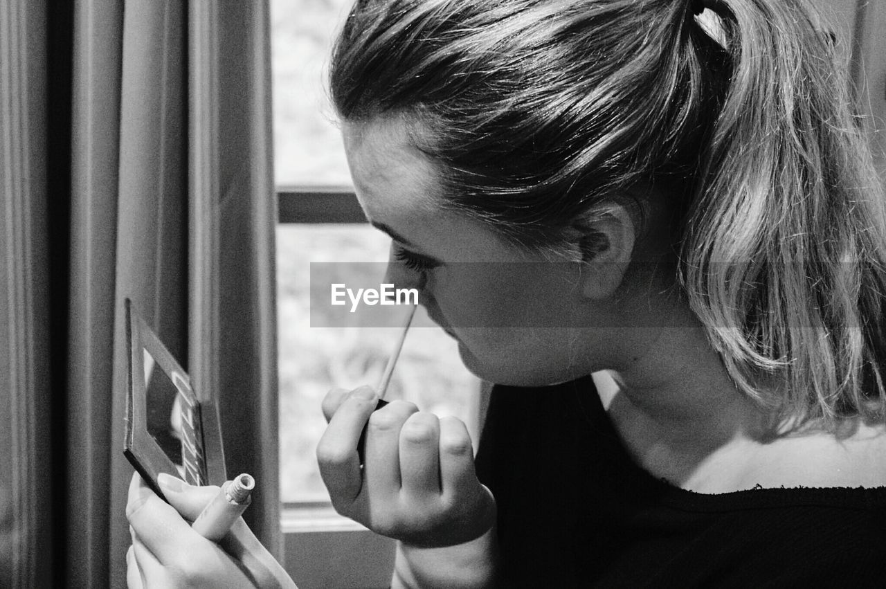 Woman looking into mirror while applying eyeliner