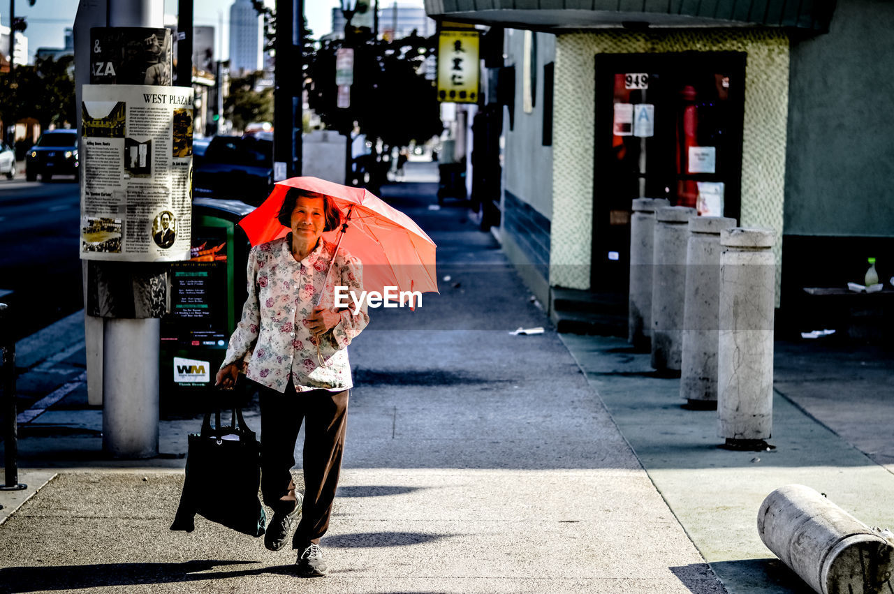 WOMAN WALKING ON FOOTPATH IN CITY