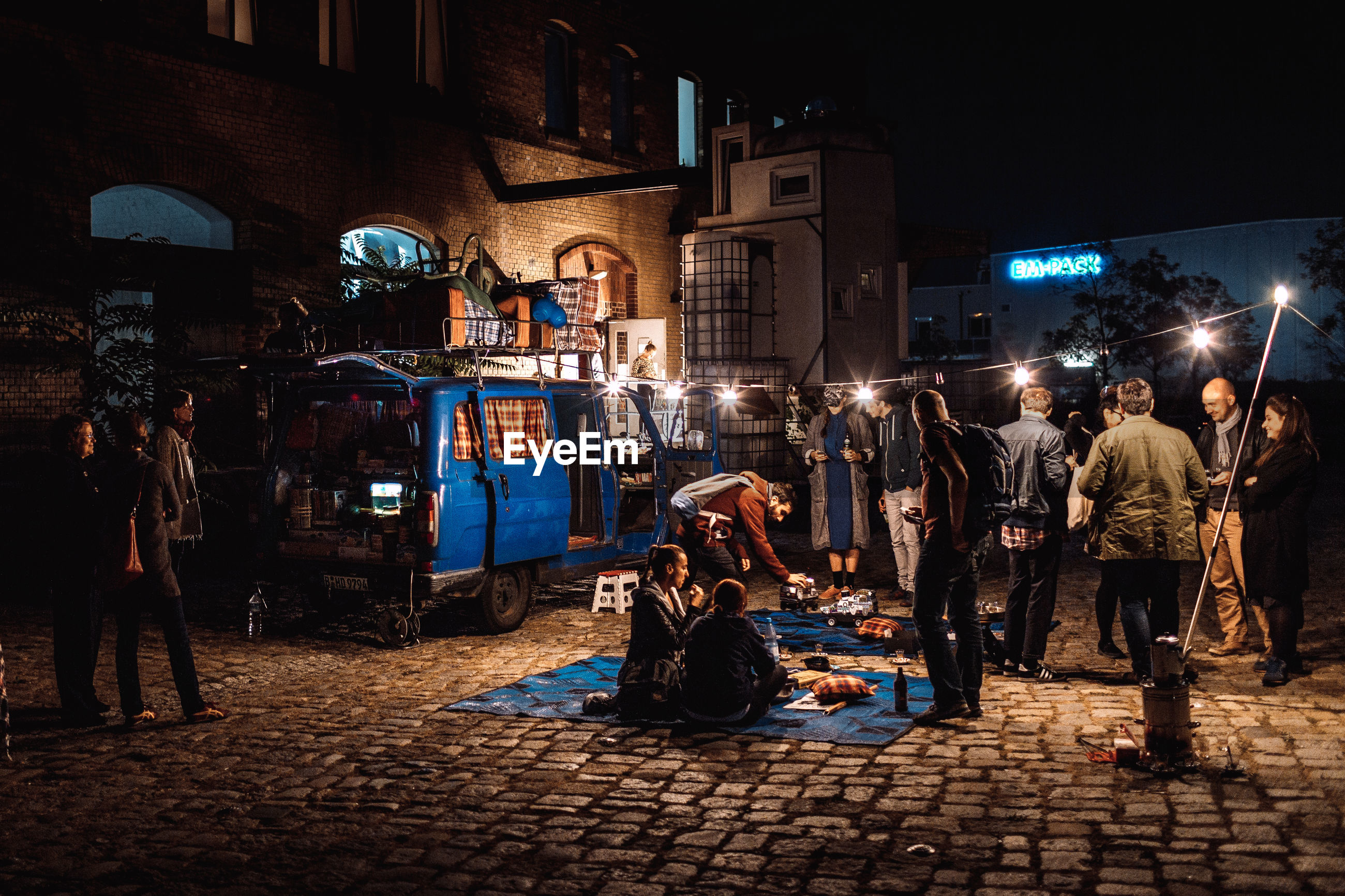illuminated, night, architecture, building exterior, built structure, men, street, city, cobblestone, person, full length, city street, group of people, sky, outdoors, city life, performance