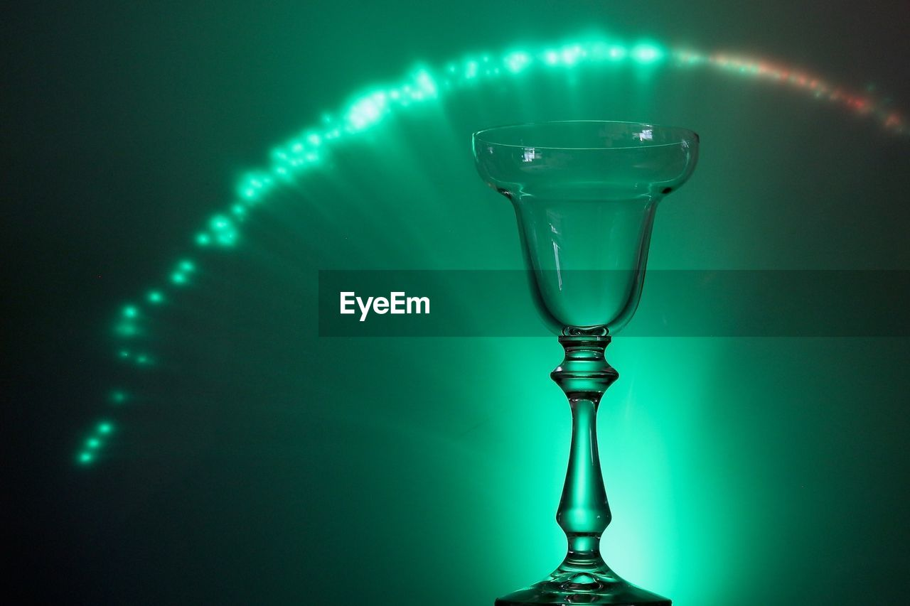 Drinking glass against illuminated green background