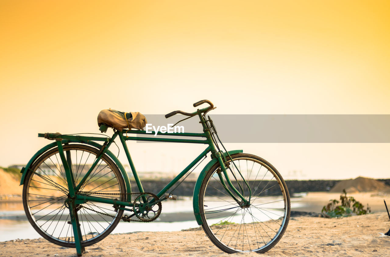 Bicycle Parked By Stream Against Clear Sky During Sunset