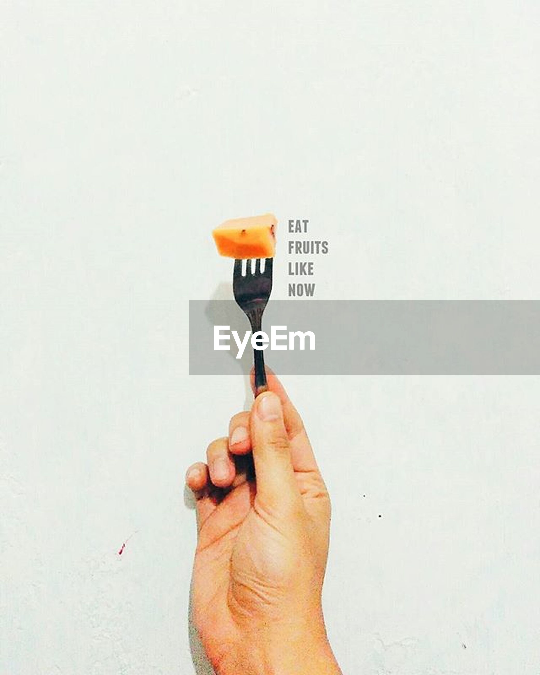person, holding, studio shot, part of, copy space, cropped, white background, human finger, unrecognizable person, communication, lifestyles, close-up, personal perspective, men, wall - building feature, food and drink, text