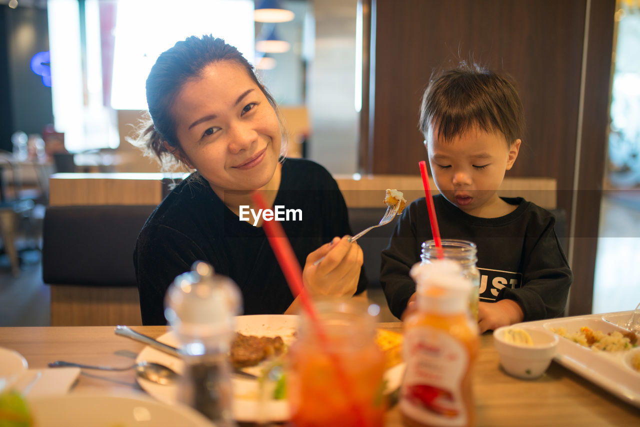 Happy Mother And Son Eating Lunch At Table