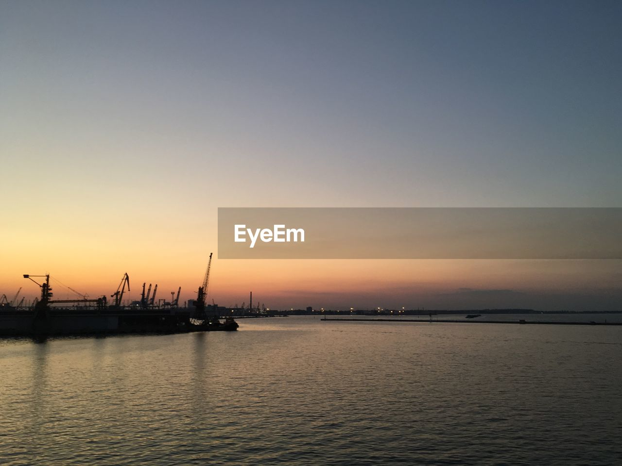 sunset, water, waterfront, silhouette, tranquility, nature, sea, nautical vessel, scenics, transportation, commercial dock, outdoors, sky, tranquil scene, beauty in nature, harbor, no people, clear sky, architecture, day, drilling rig