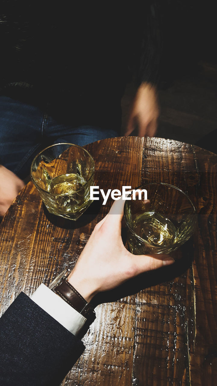 food and drink, table, refreshment, indoors, wood - material, human hand, drink, drinking glass, close-up, freshness, real people, food, healthy eating, one person, day, herbal tea, ready-to-eat, mint tea