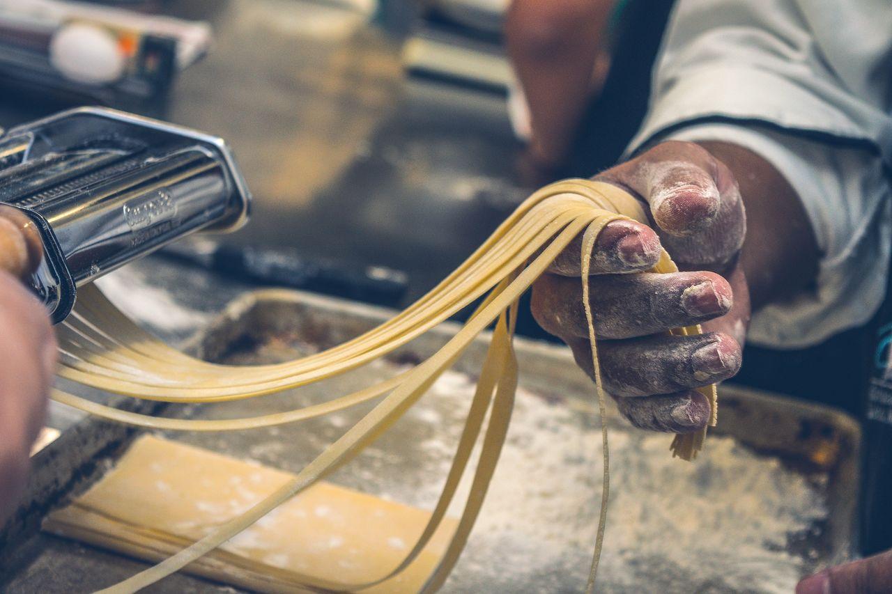 Cropped Hand Preparing Pasta In Machinery