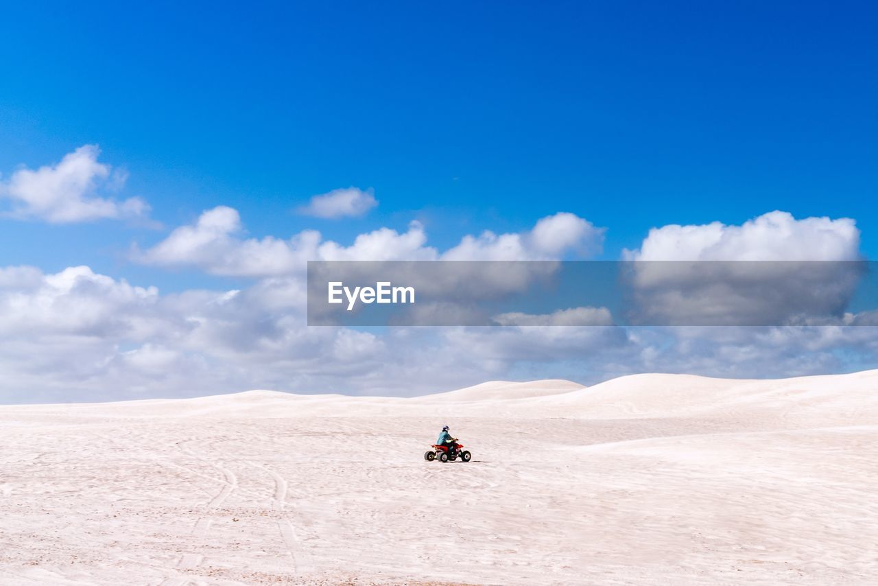 sky, cloud - sky, scenics - nature, desert, land, landscape, environment, day, nature, beauty in nature, non-urban scene, climate, sand, arid climate, mode of transportation, real people, transportation, blue, travel, remote, outdoors, riding, salt flat