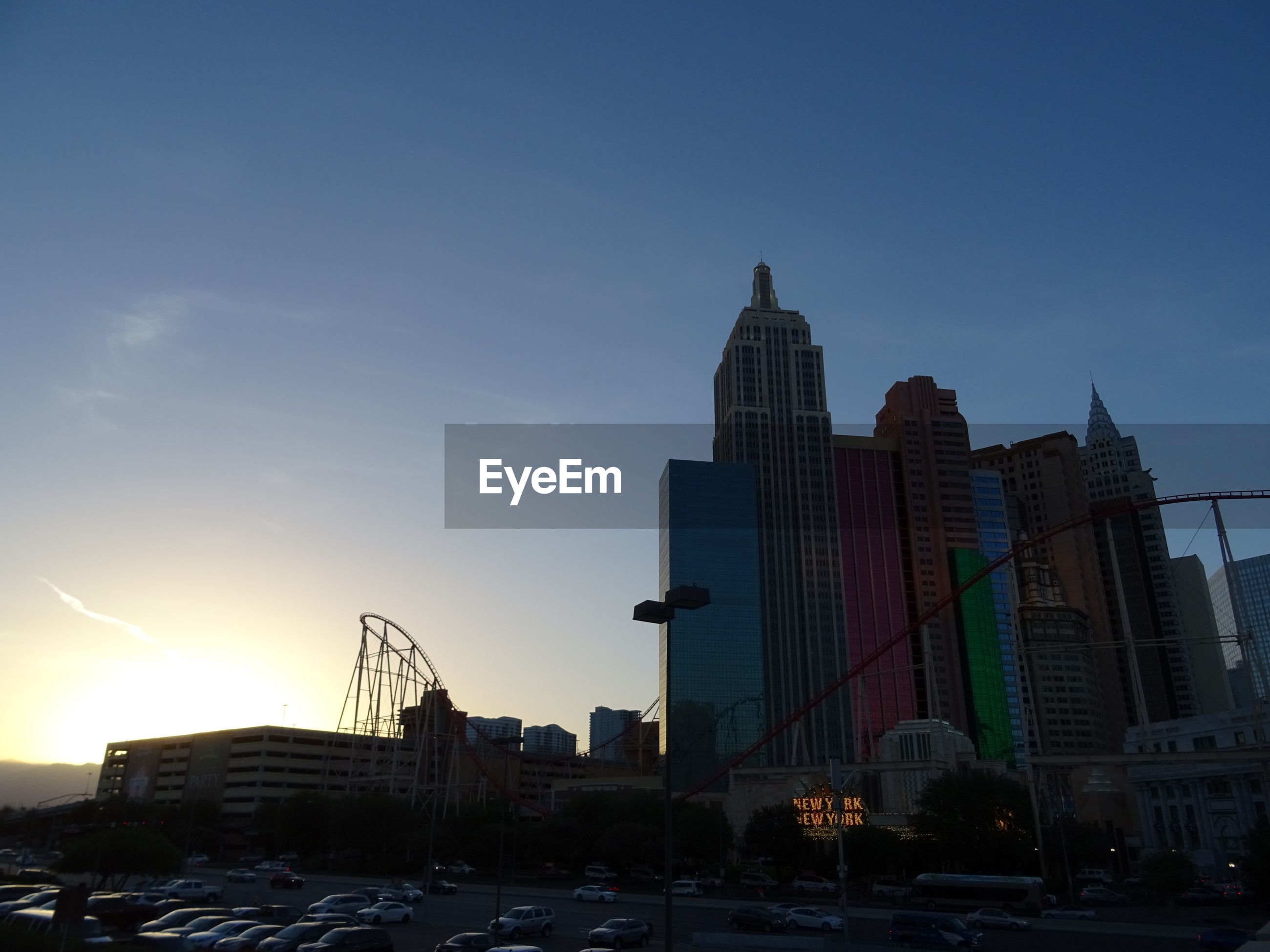 BUILDINGS IN CITY AGAINST SKY AT SUNSET