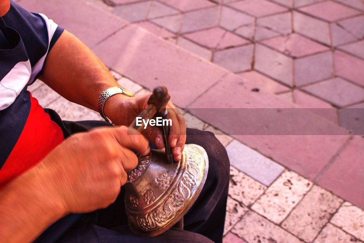 Midsection Of Man Carving Metal While Sitting On Footpath