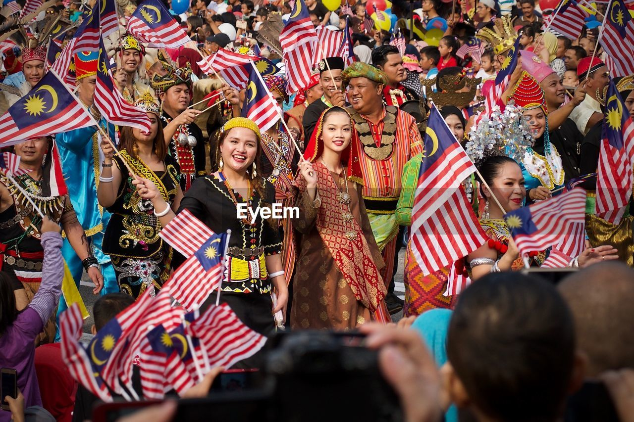 group of people, large group of people, men, real people, holding, crowd, women, emotion, happiness, arts culture and entertainment, togetherness, enjoyment, smiling, young women, front view, young adult, males