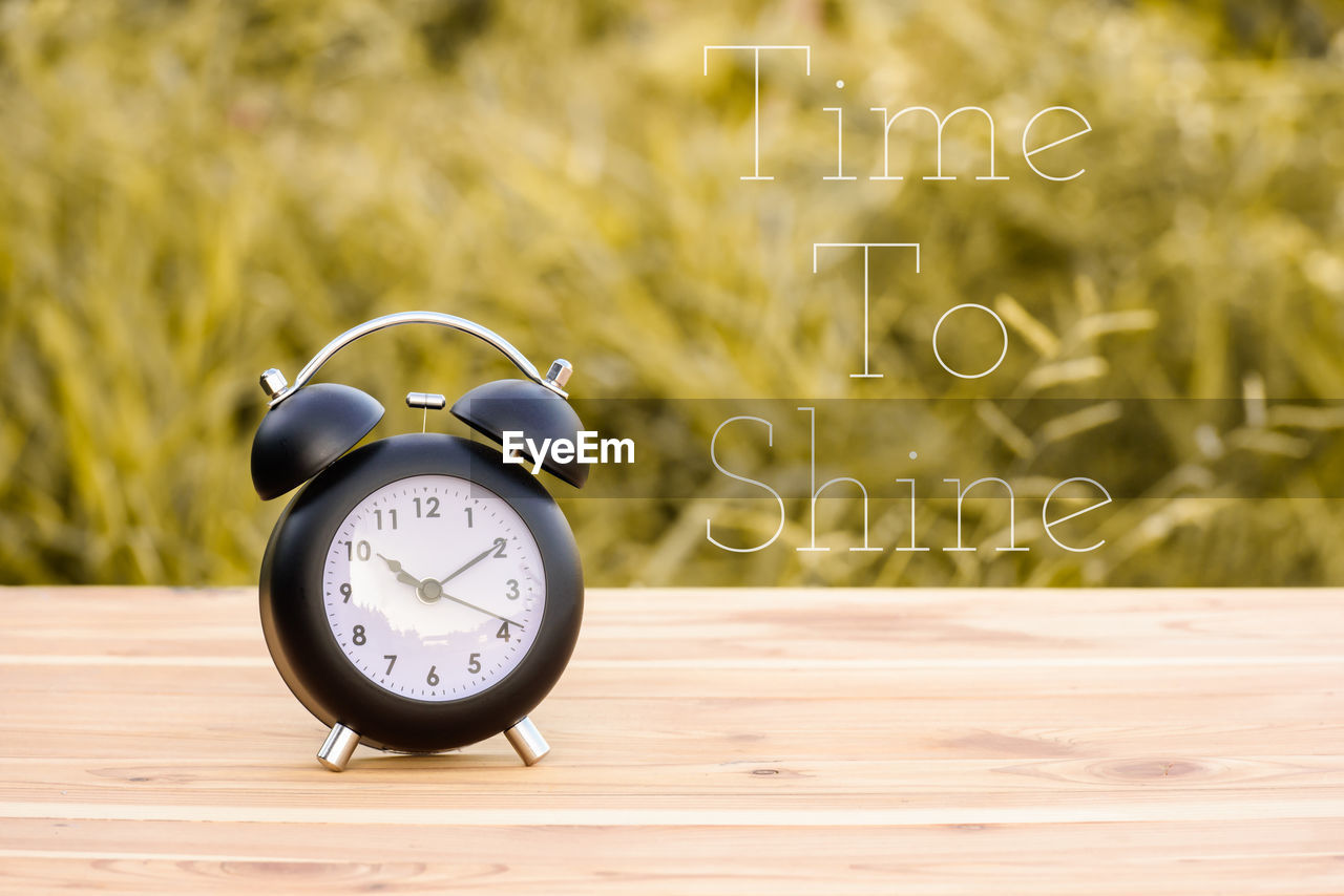 alarm clock, clock, focus on foreground, number, table, time, no people, communication, close-up, still life, day, accuracy, technology, nature, plant, outdoors, wood - material, animal, shape, single object, minute hand, clock face