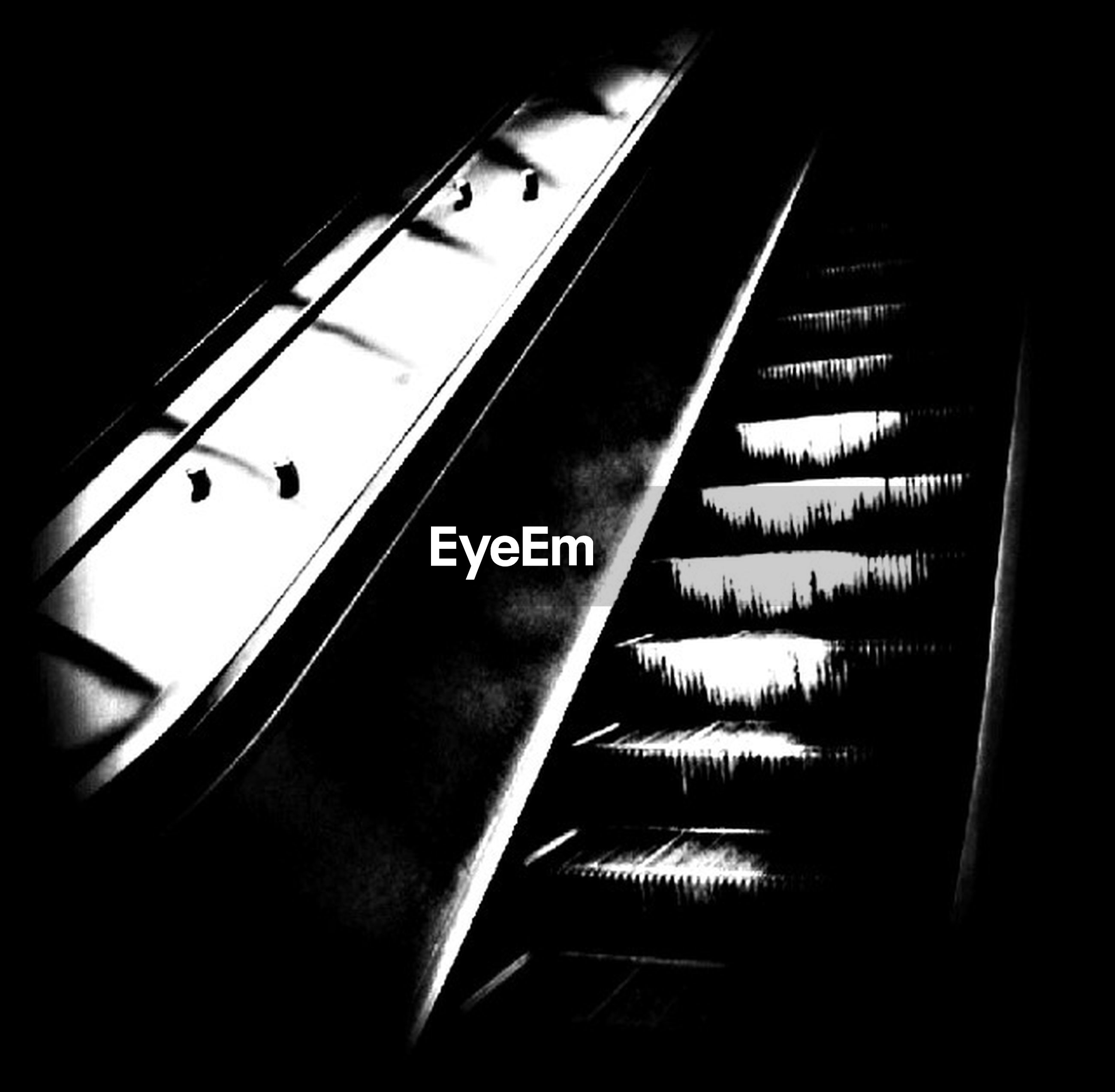 indoors, low angle view, technology, illuminated, no people, close-up, music, modern, staircase, built structure, connection, architecture, in a row, dark, part of, arts culture and entertainment, escalator, night, piano key, lighting equipment