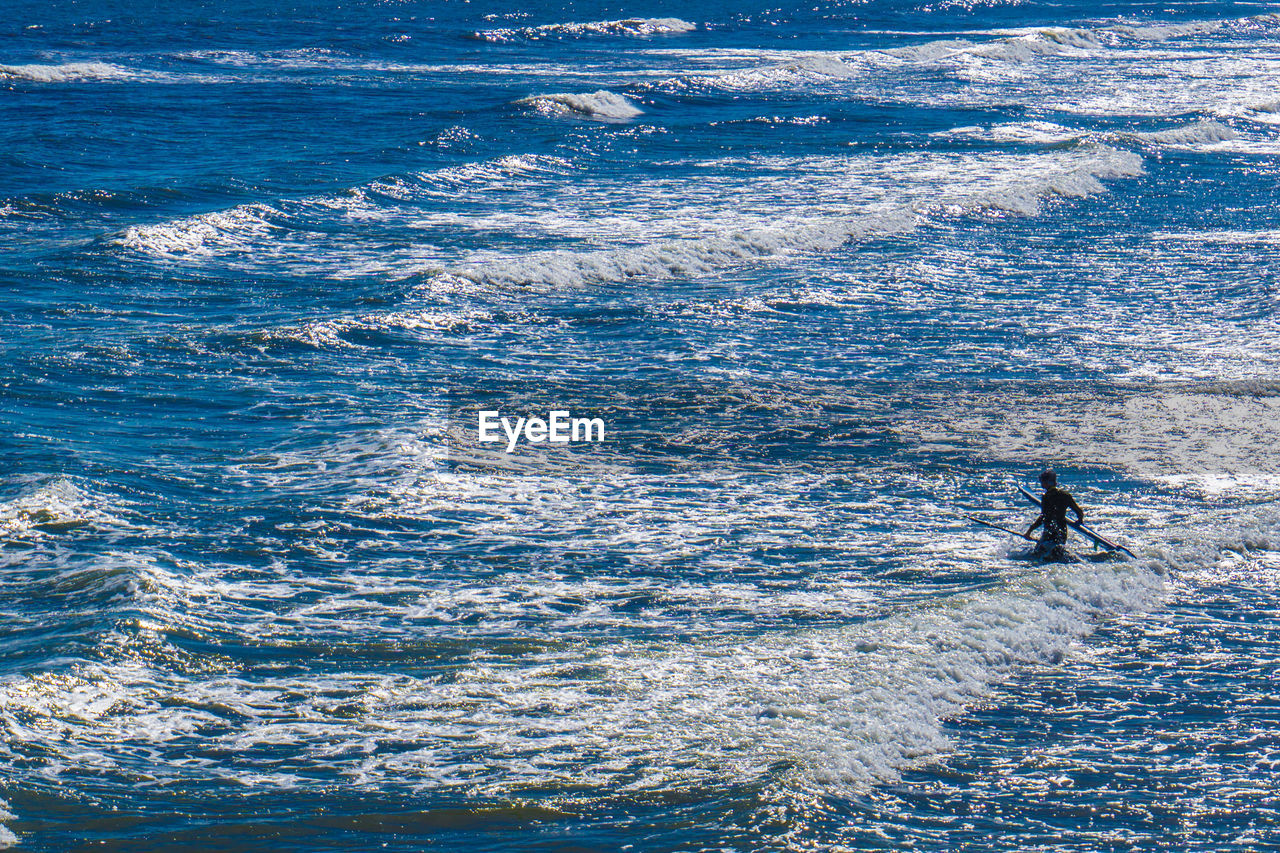 sea, water, motion, sport, wave, aquatic sport, beauty in nature, surfing, day, leisure activity, one person, lifestyles, nature, real people, waterfront, outdoors, high angle view, blue