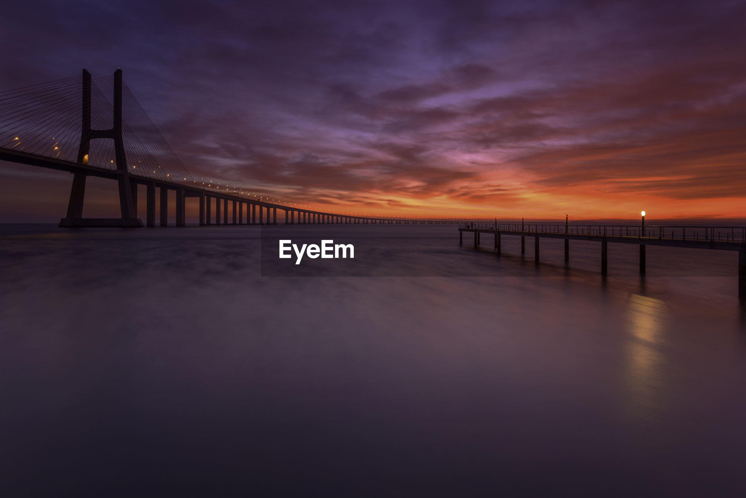 BRIDGE OVER CALM SEA AGAINST SUNSET SKY