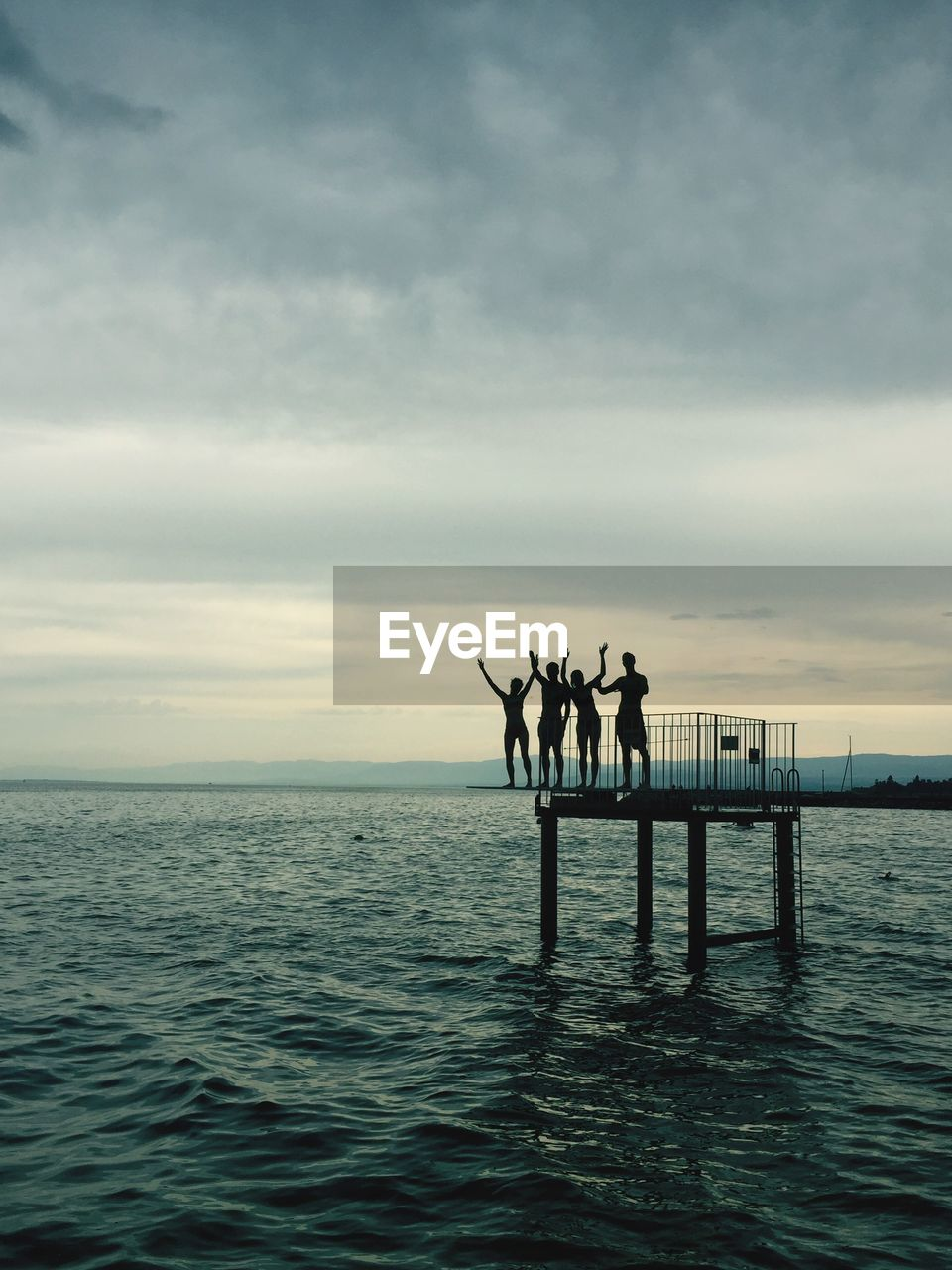 water, sky, sea, waterfront, real people, beauty in nature, cloud - sky, scenics - nature, group of people, men, horizon, silhouette, horizon over water, lifestyles, standing, leisure activity, nature, sunset, pier, outdoors, arms raised