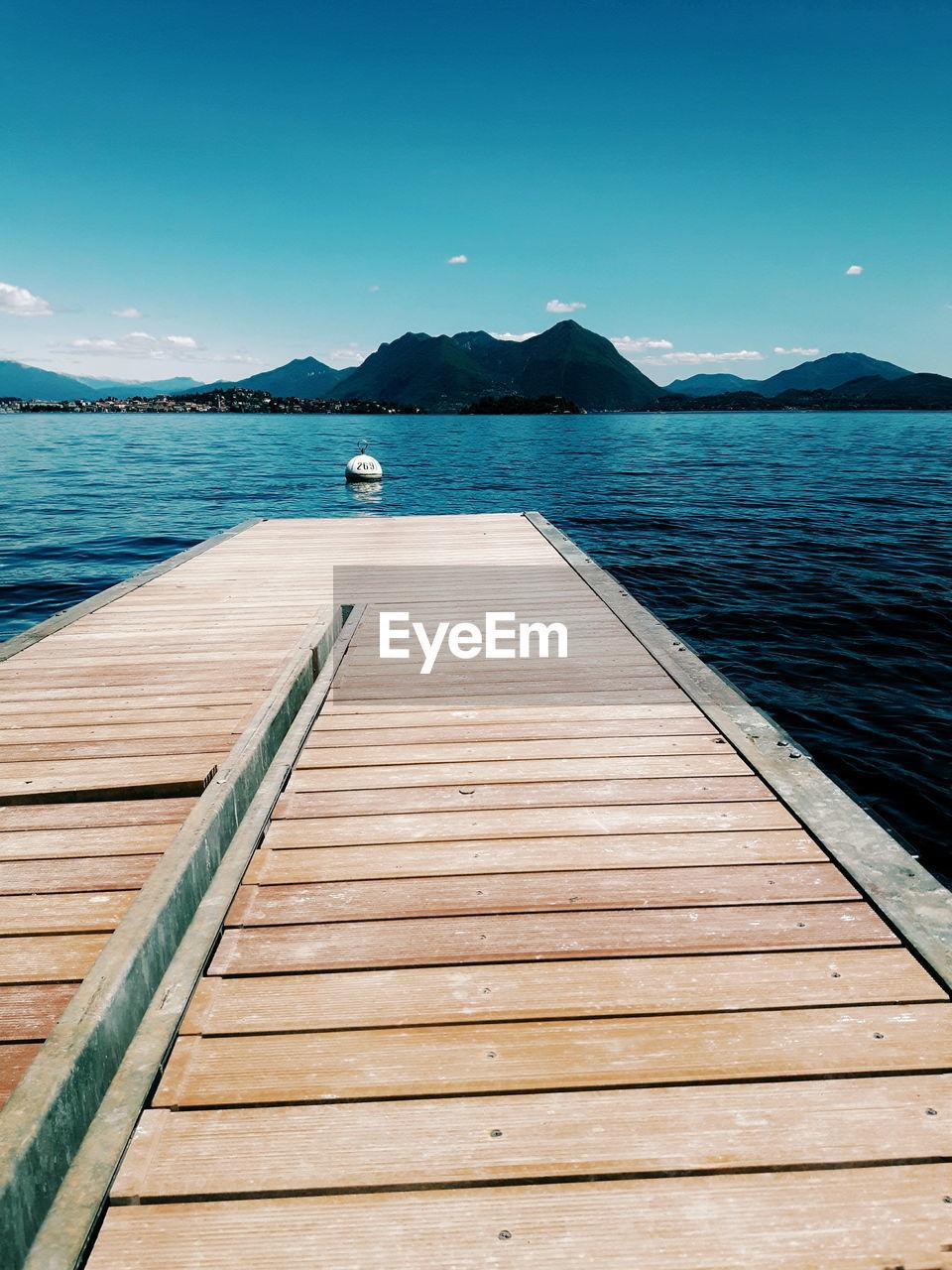 Pier on lake against blue sky
