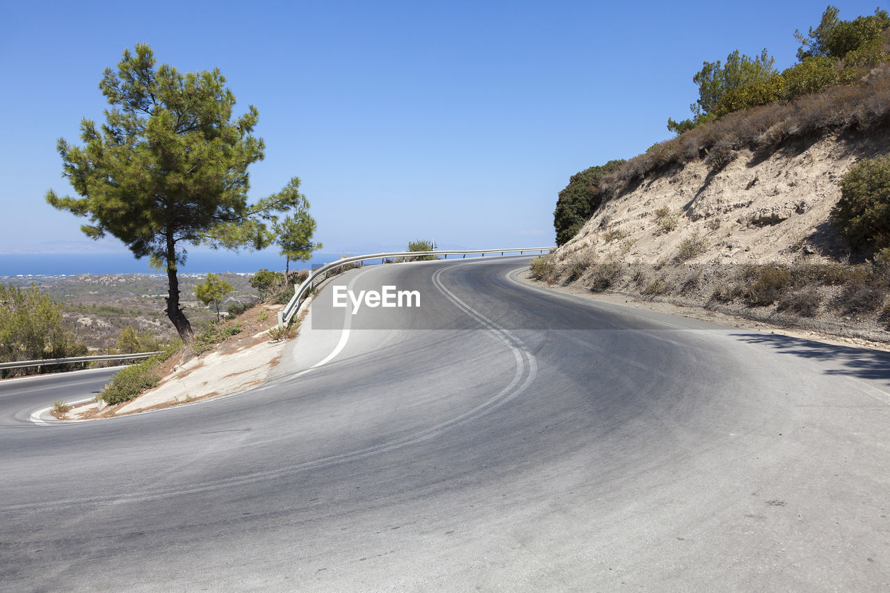 View Of Curved Road By Mountain Against Clear Sky