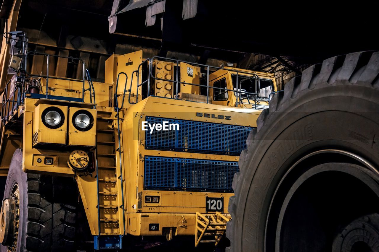 transportation, mode of transportation, yellow, land vehicle, no people, industry, machinery, outdoors, architecture, tire, day, truck, metal, built structure, business, motor vehicle, commercial land vehicle, nature, wheel