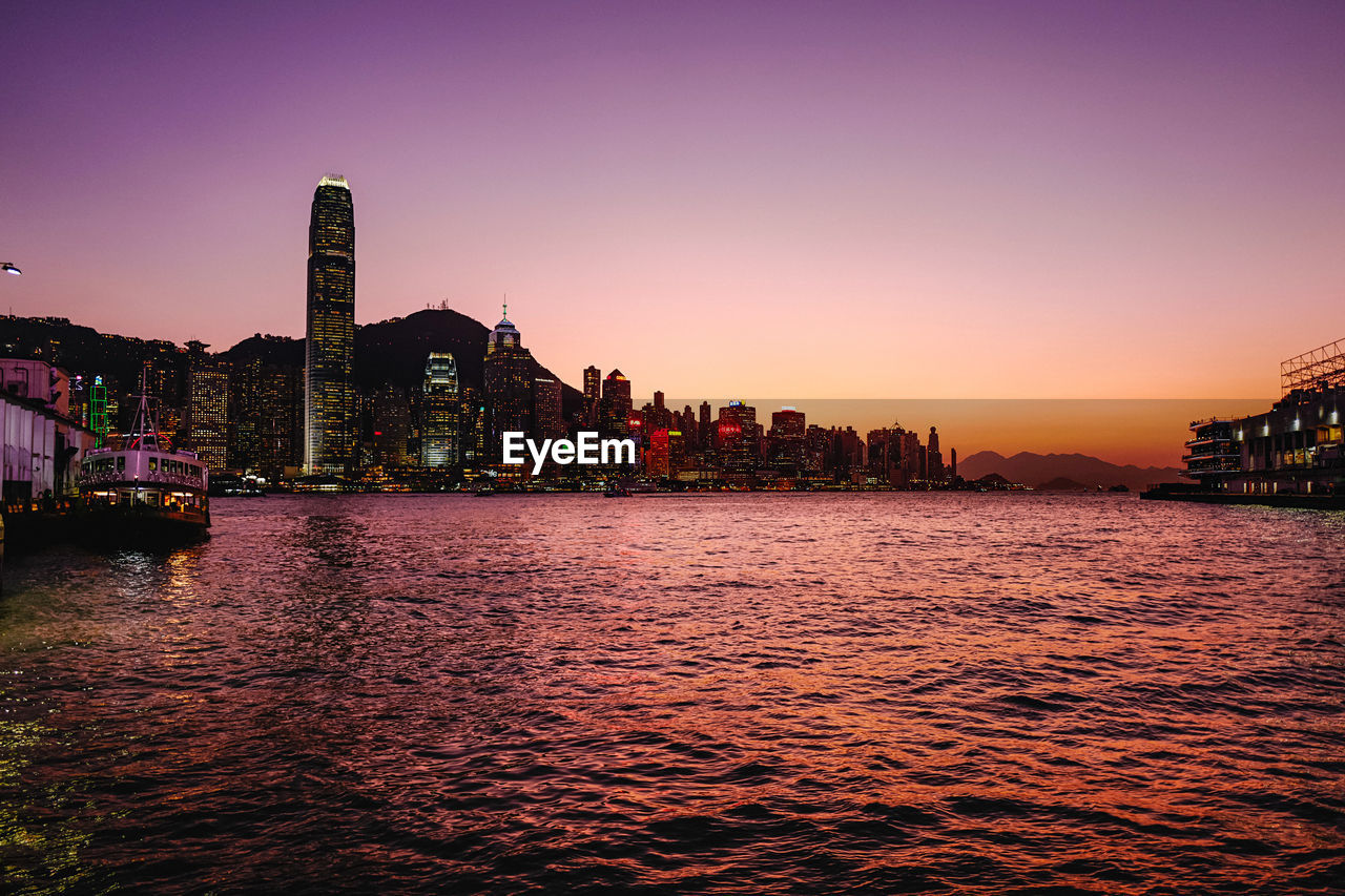 building exterior, architecture, built structure, sky, sunset, water, waterfront, city, building, nature, office building exterior, no people, tall - high, cityscape, skyscraper, clear sky, illuminated, orange color, sea, outdoors, financial district
